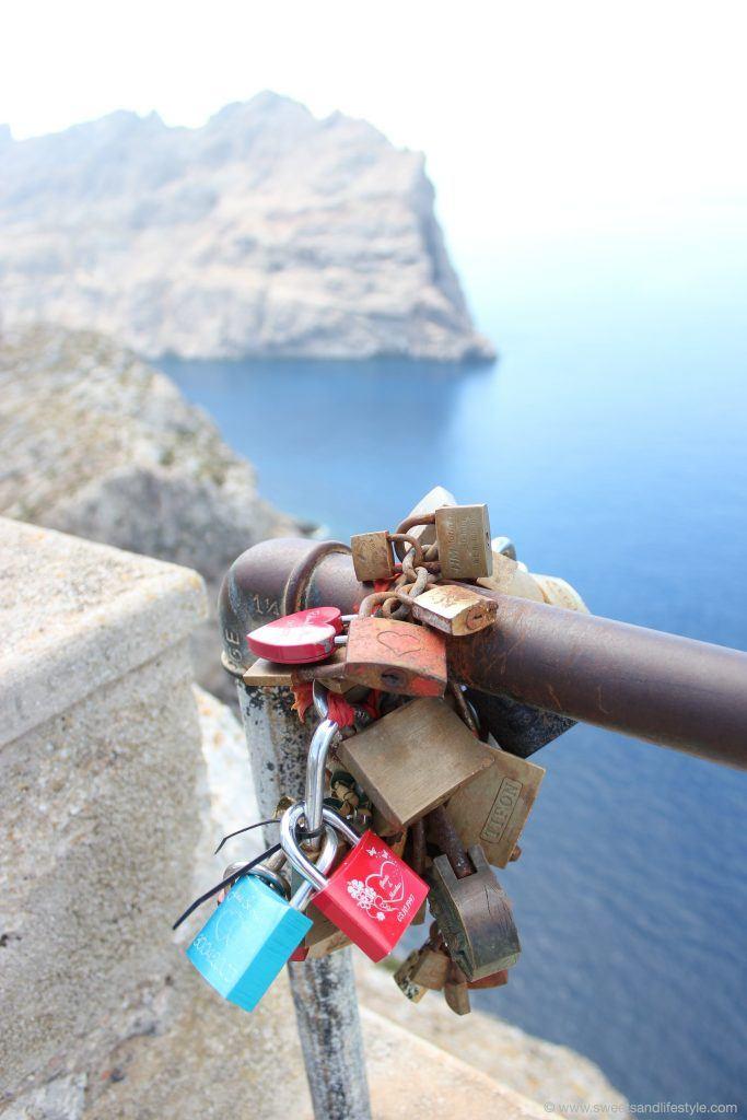 Befestige Liebesschlösser am Geländer auf Cap Formentor auf Mallorc