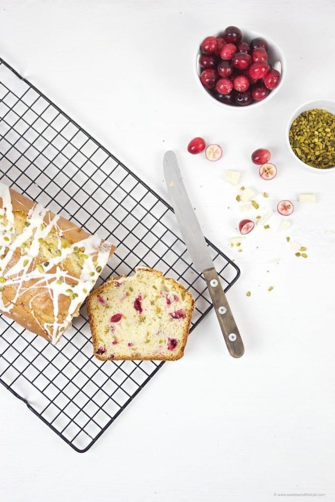 Saftiger Cranberry Pistazien Kastenkuchen mit einer Glasur aus weißer Schokolade obendrauf von Sweets and Lifestyle