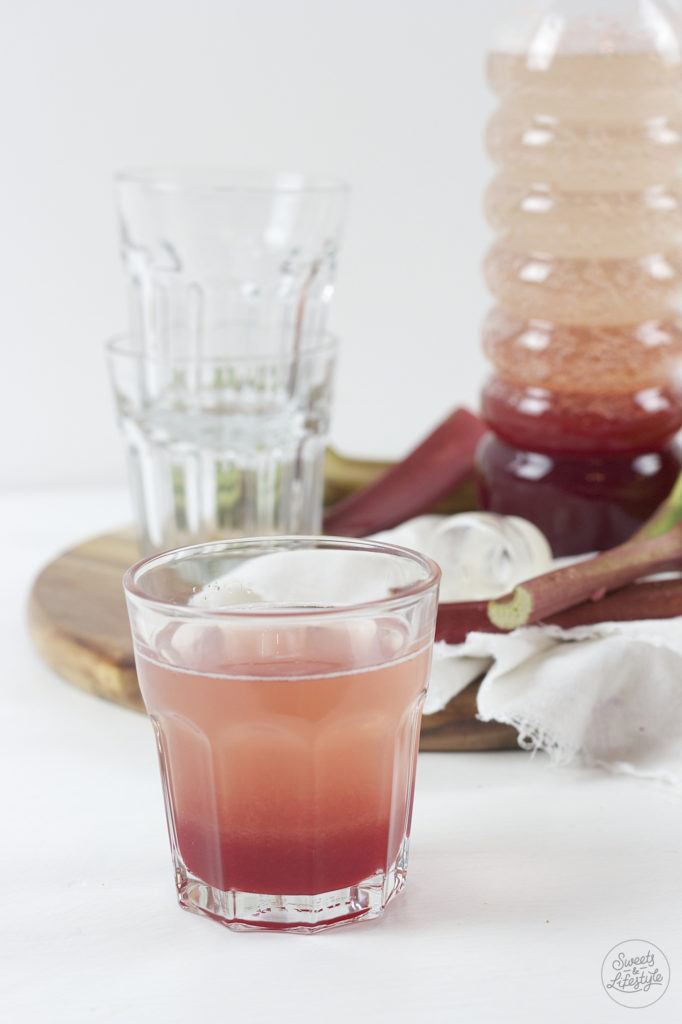 Ein Glas erfrischender Rhabarber Himbeer Sirup mit Wasser verduennt von Sweets and Lifestyle