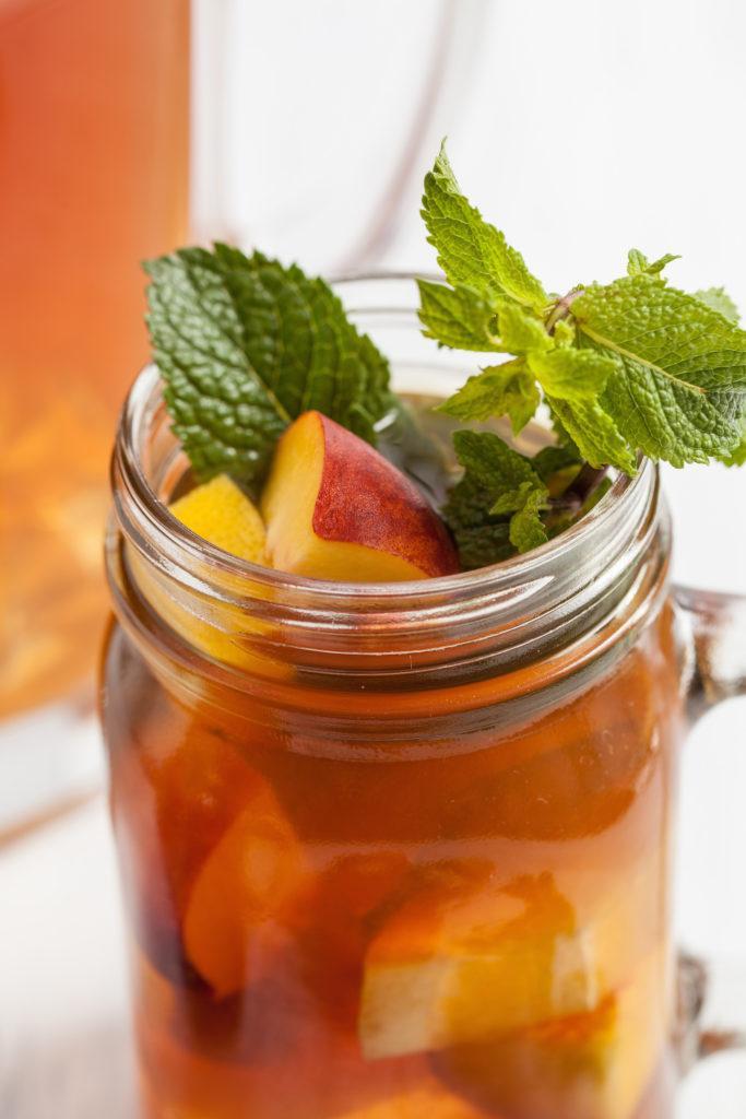Erfrischender Pfirsicheistee serviert mit Pfirsichstuecken und frischer von Sweets and Lifestyle