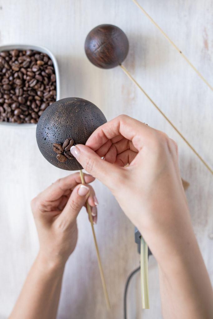 Anbringen der einzelnen Kaffeebohnen auf der Styroporkugel für Dekobälle aus Kaffeebohnen