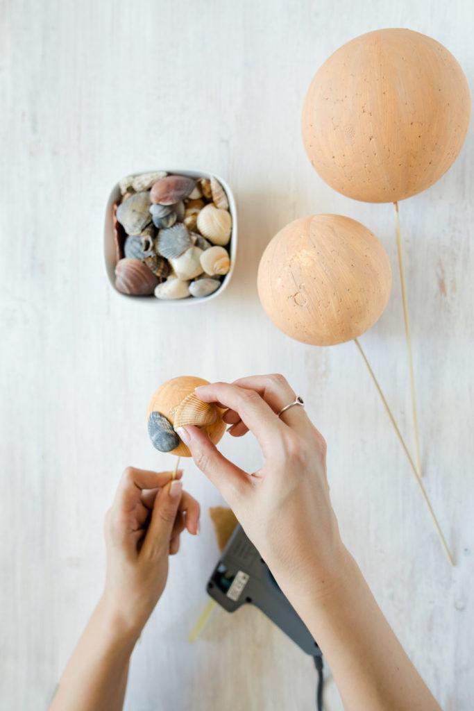 Anbringen der einzelnen Muscheln aus dem Urlaub auf der Styroporkugeln