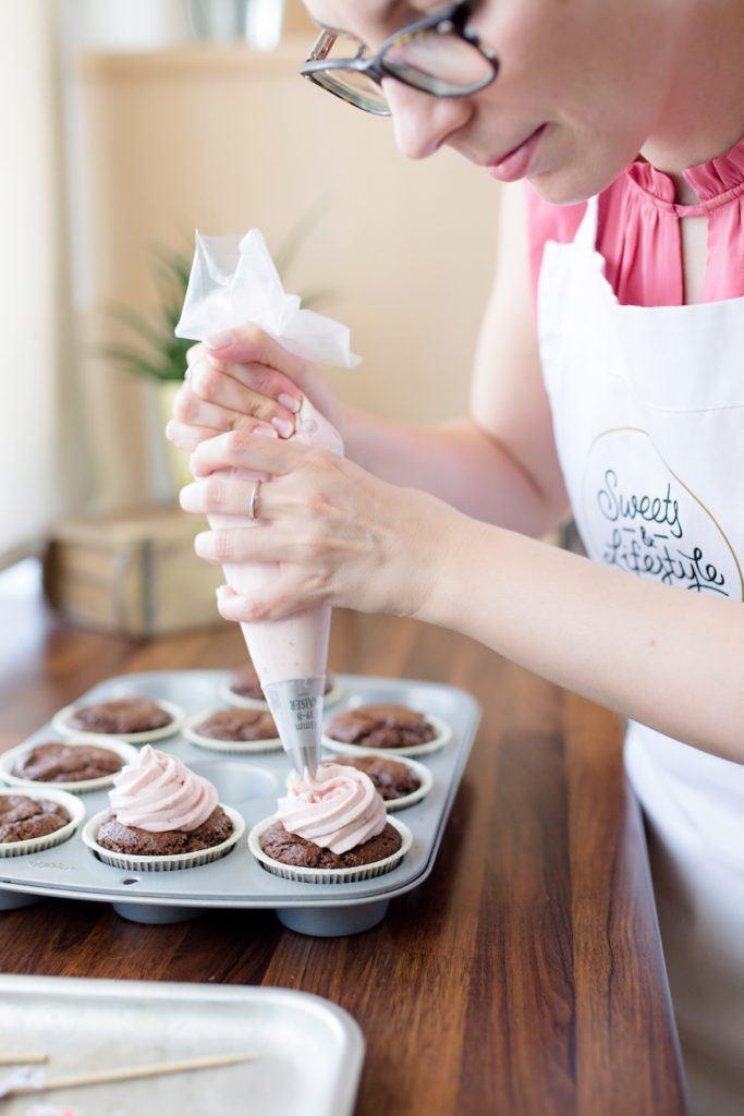 Verena von Sweets & Lifestyle® beim Aufdressieren von ihrem Himbeer Topping auf die Schoko-Himbeer-Cupcakes