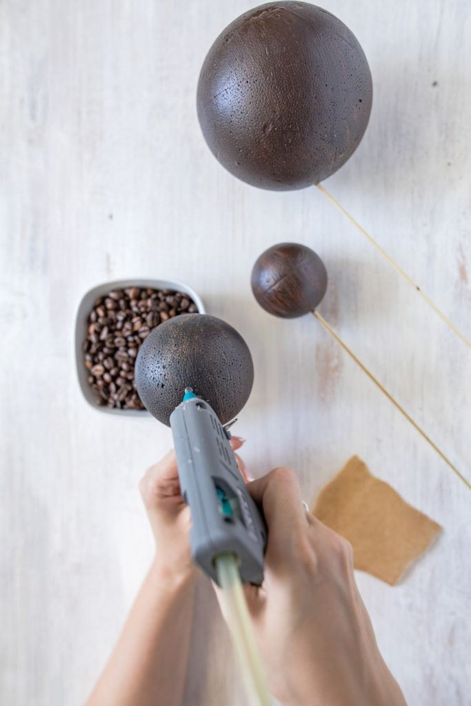Verwendung einer Heißklebepistole zum Anbringen der Kaffeebohnen auf den Strypoporkugeln