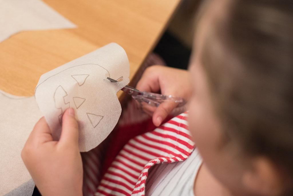 Junge Teilnehmerin beim Ausschneiden der Kürbisvorlage für die pikanten Handpies beim Halloween Back-Workshop für Kinder von Sweets & Lifestyle®