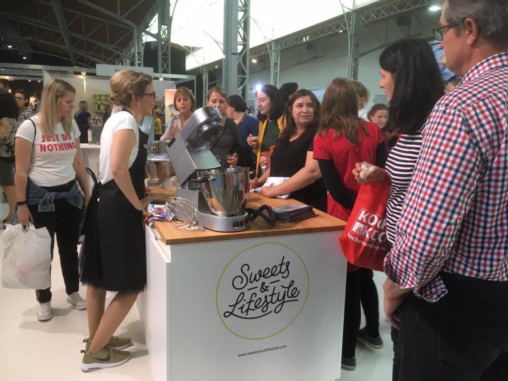 Besucherinnen tummeln sich um den KENWOOD Stand mit Foodbloggerin Verena Pelikan von Sweets & Lifestyle® auf der Kuchenmesse Wien