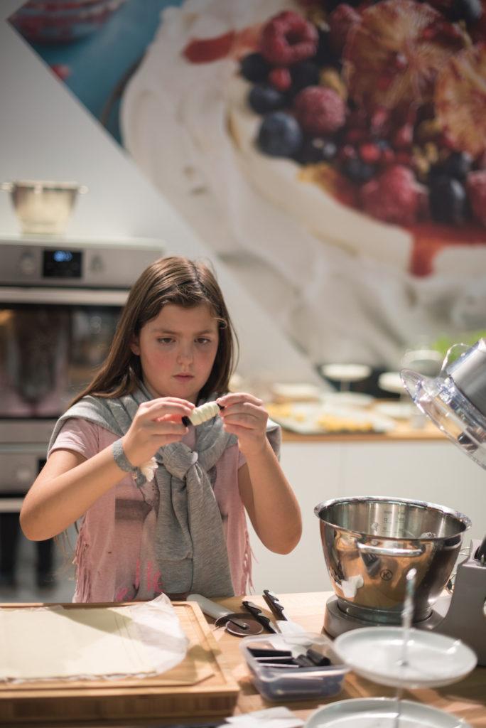 Junge Besucherin der Kuchenmesse Wien beim Schaumrollen Wickeln am KENWOOD Stand mit Sweets & Lifestyle®