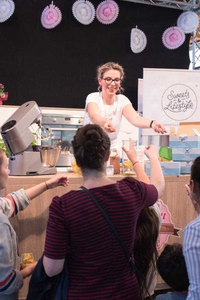 Verena Pelikan lässt das Publikum ihre auf der Showbühne der Kuchenmesse Wien zubereiteten Desserts im Glas verkosten