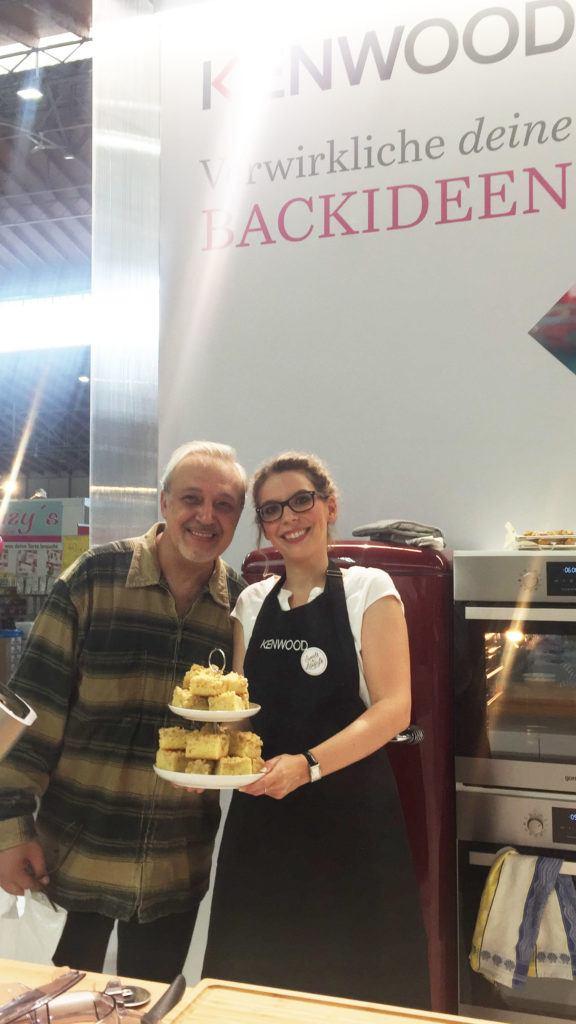 Die beliebte Foodbloggerin Verena Pelikan von Sweets & Lifestyle® mit ihrem Apfelkuchen und einem begeisterten Besucher am Kenwood Stand auf der Kuchenmesse Wien