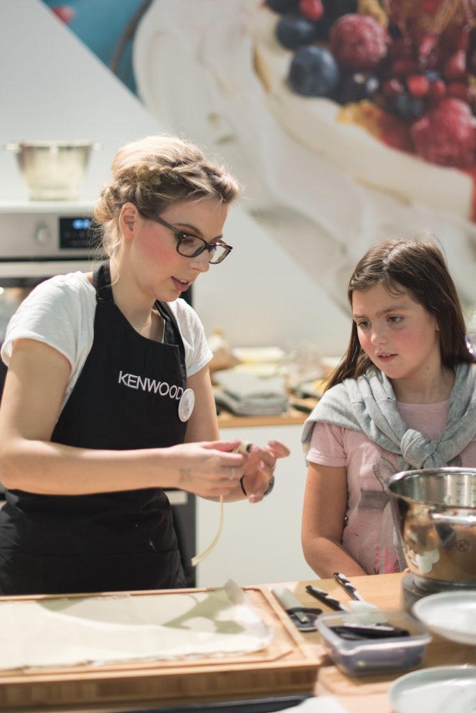 Verena Pelikan von Sweets & Lifestyle® zeigt einer jungen Besucherin wie man den Blätterteig für Schaumrollen wickelt