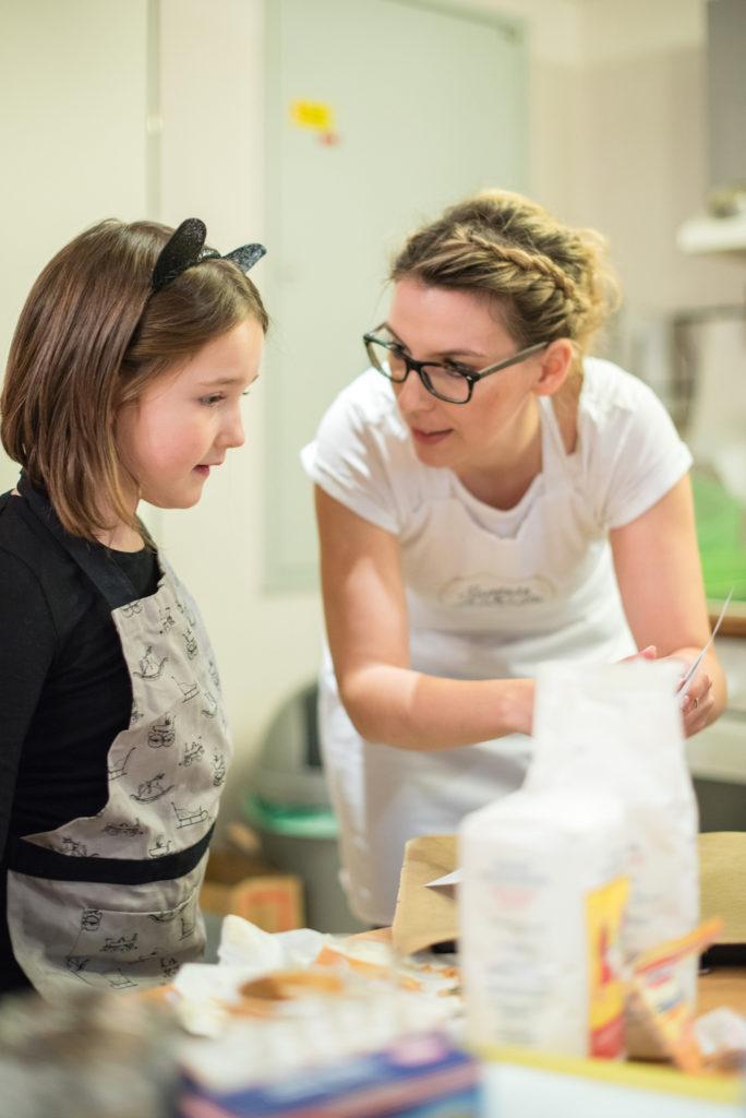 Verena Pelikan von Sweets & Lifestyle® mit interessierter Teilnehmerin bei ihrem Halloween Back-Workshop für Kinder
