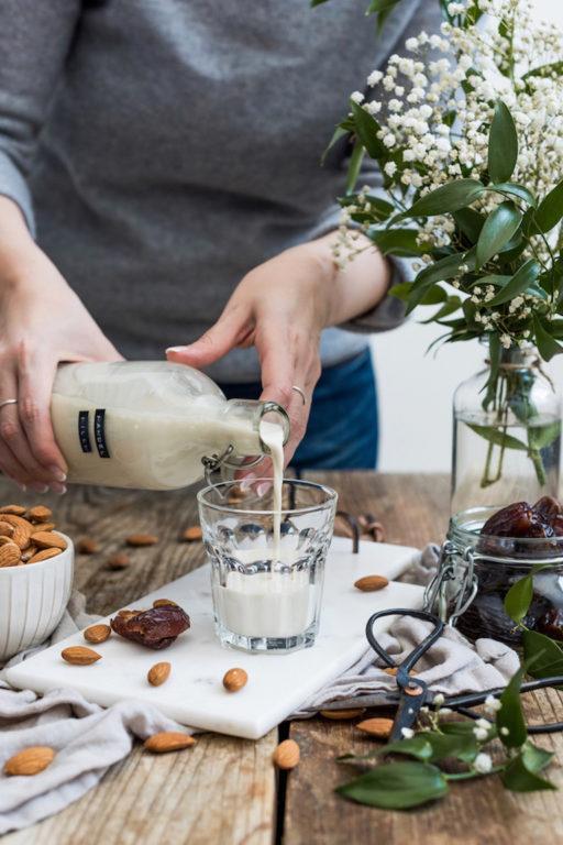 Verena von Sweets & Lifestyle® beim Einschenken ihrer selbst gemachten Mandelmilch in ein Glas