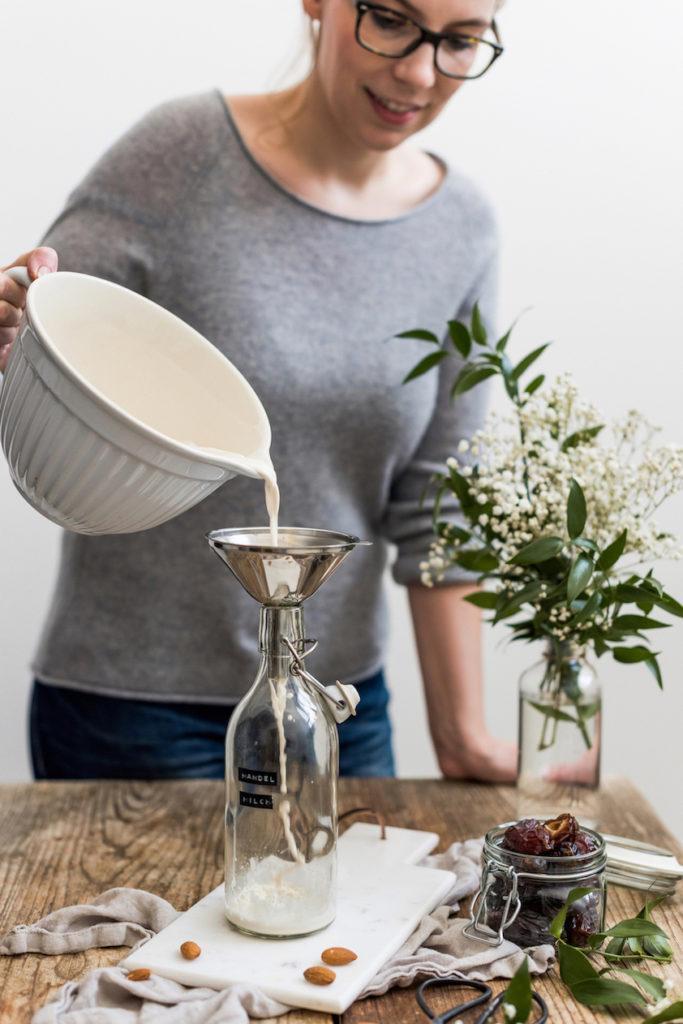Verena von Sweets & Lifestyle® füllt ihr selbst gemachte Mandelmilch in eine Flasche