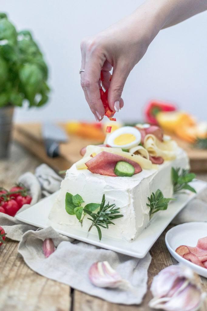 Paprikastücke als Garnierung auf der pikanten Brottorte verteilen wie Verena von Sweets & Lifestyle®