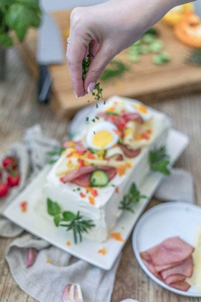 Schnittlauchröllchen als Verzierung auf der pikanten Brottorte verteilen wie Verena von Sweets & Lifestyle®