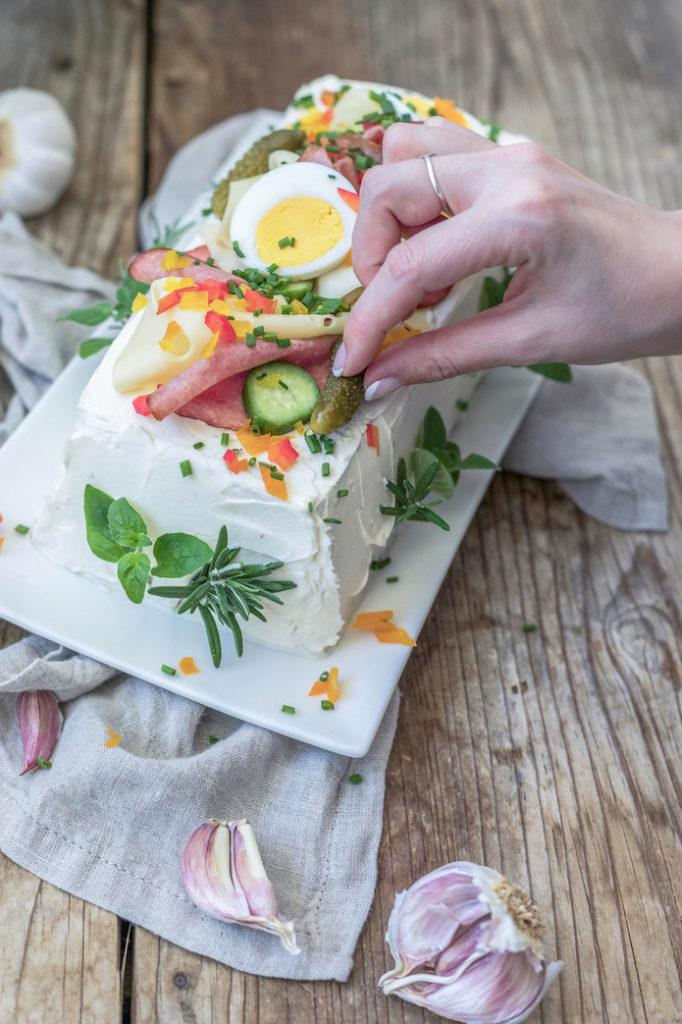 Verena von Sweets & Lifestyle® beim Garnieren ihrer pikanten Brottorte die sie mit verschiedenen Aufstrichen gefüllt hat
