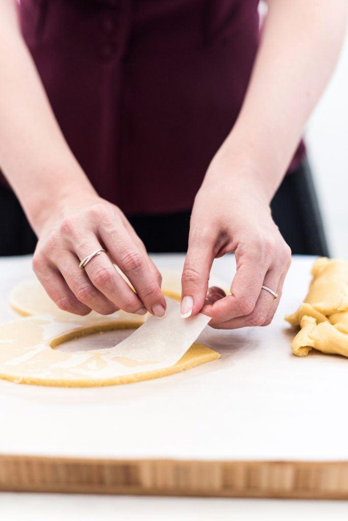 Verena von Sweets & Lifestyle® beim Abziehen der Backpapierschablone vom Mürbteig für ihren Number Cake