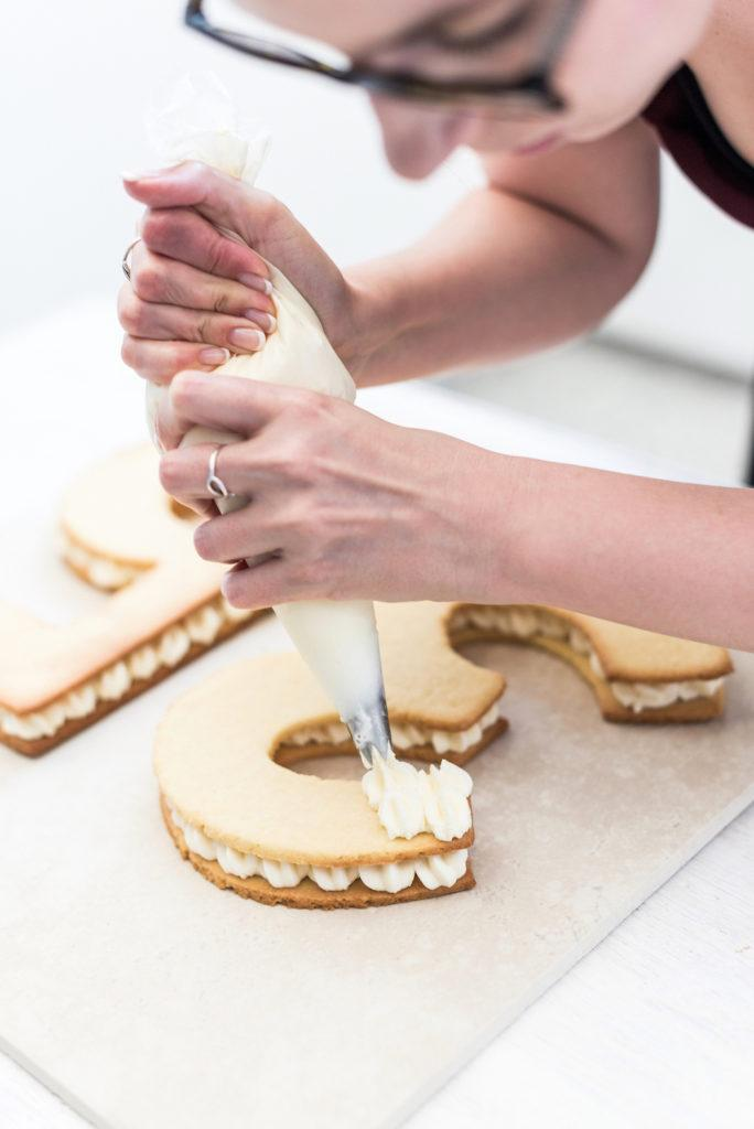 Verena von Sweets & Lifestyle® spritzt die Number Cake Fülle auf die Mürbteigziffern für ihren Number Cake