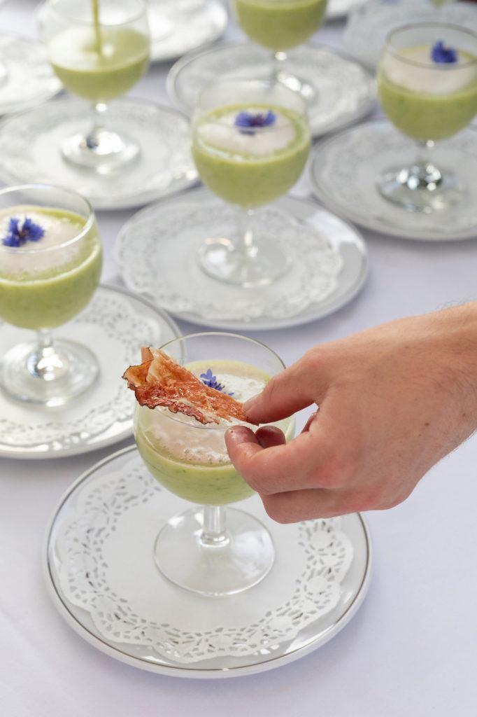 Garnieren der Erbsencremesuppe mit Minzschaum mit einem Rohschinkenchip beim Tafeln im Weinviertel