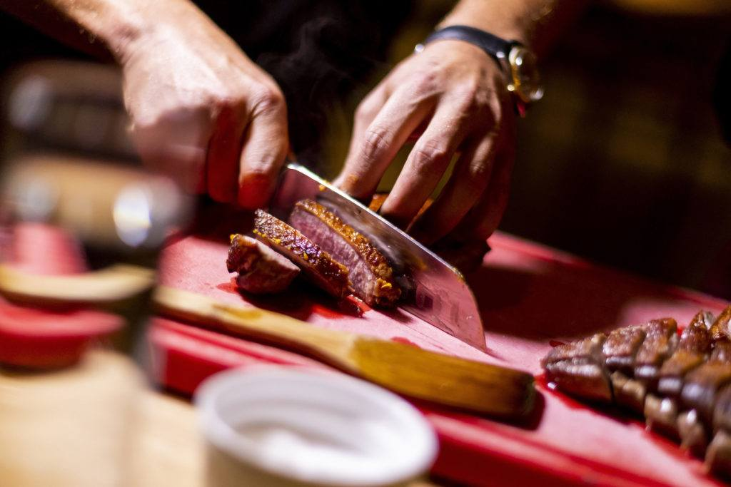 Knusprige Ente mit Sesam gewürzt mit Shan' Shi Produkten wird mit einem scharfen Messer aufgeschnitten