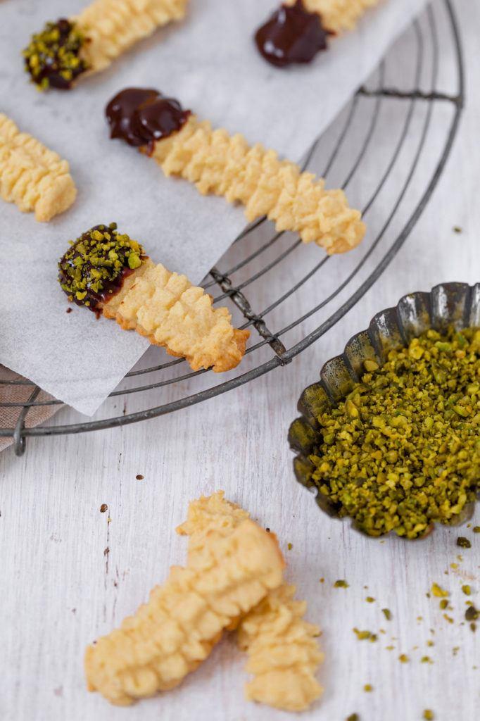 Leckeres Spritzgebäck nach einem Rezept von Sweets & Lifestyle® wird mit Schokolade und Nüssen verziert