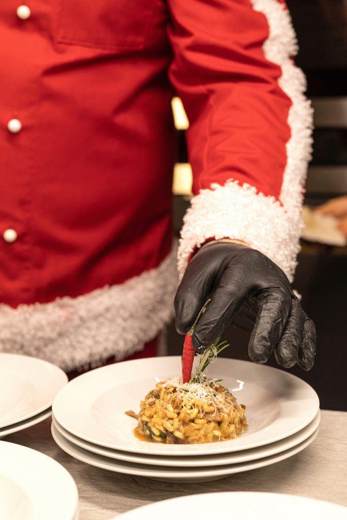 Leckeres Steinpilzrisotto wird garniert mit frischem Rosmarin, einer Chilischote und frisch geriebenen Parmesan