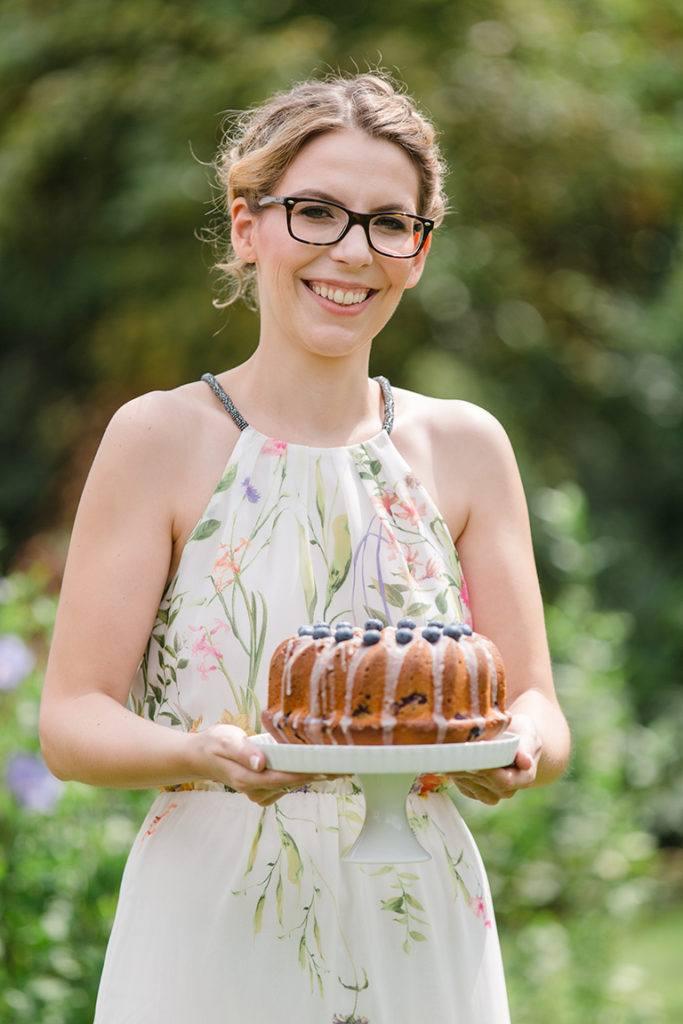 Foodbloggerin Verena Pelikan mit dem von ihr kreierten und gebackenen Gugelhupf mit Heidelbeeren