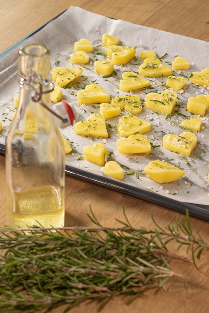 Ausgestochene Herzkartoffeln von Verena Pelikan von Sweets & Lifestyle® mit Rosmarin und Meersalz gewürzt am Backblech