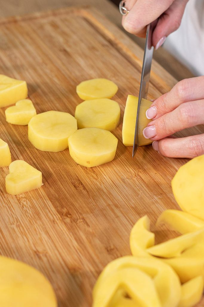 Geschälte Kartoffeln in Scheiben schneiden für die Zubereitung von Herzkartoffeln