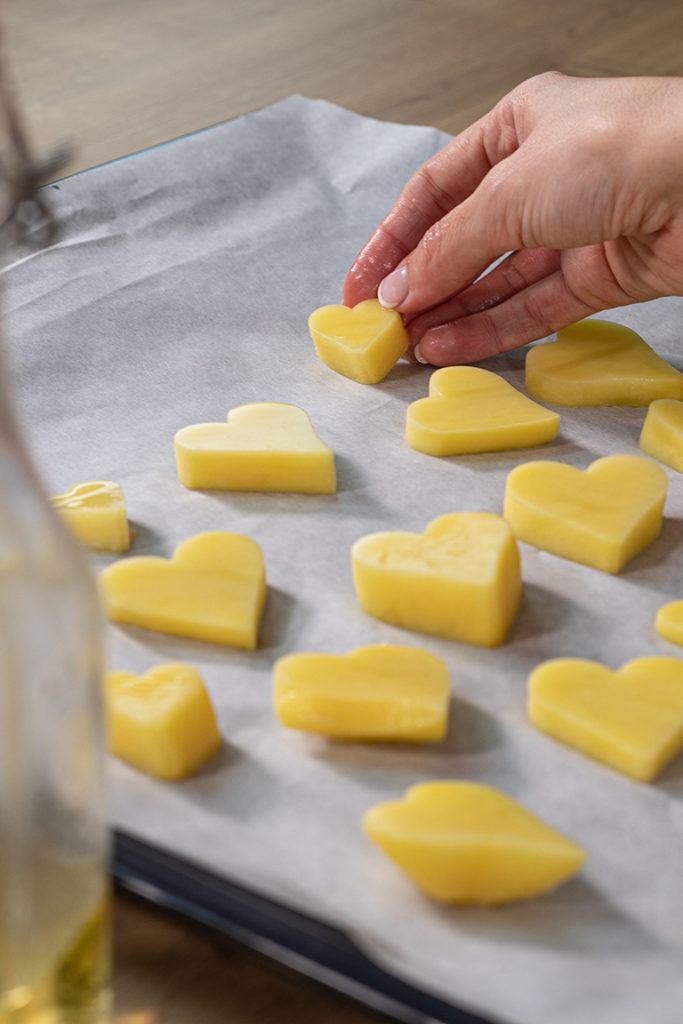 Ausgestochene Herzkartoffeln werden von Verena Pelikan von Sweets & Lifestyle® auf das mit Backpapier ausgelegte Backblech gelegt