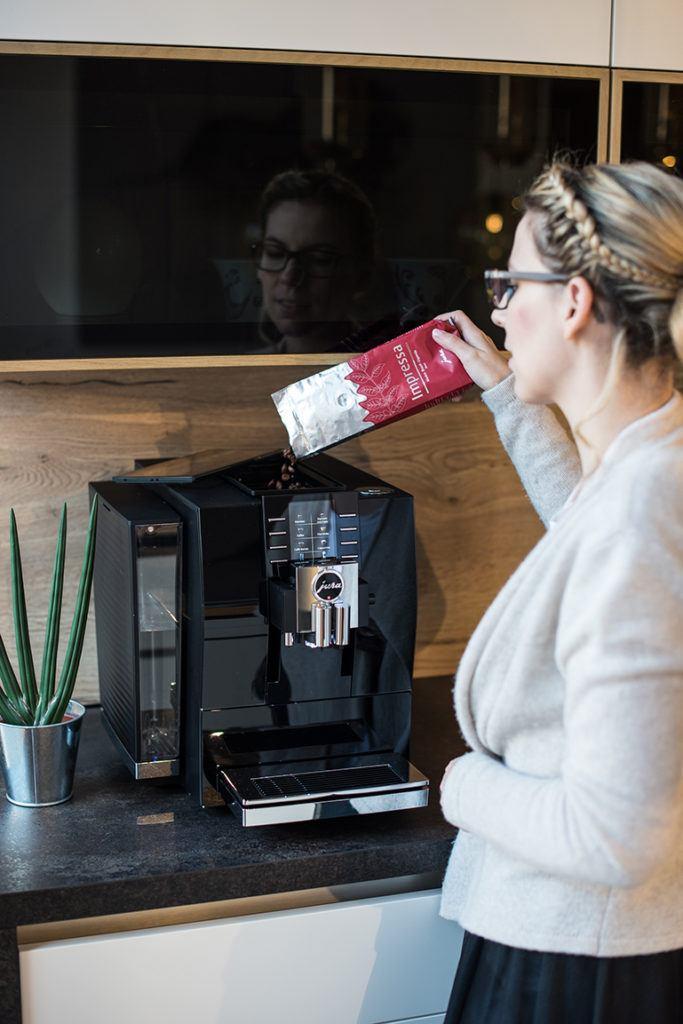 Verena Pelikan füllt im SchlossStudio Kaffeebohnen in ihren Jura Z6 Kaffeevollautomaten