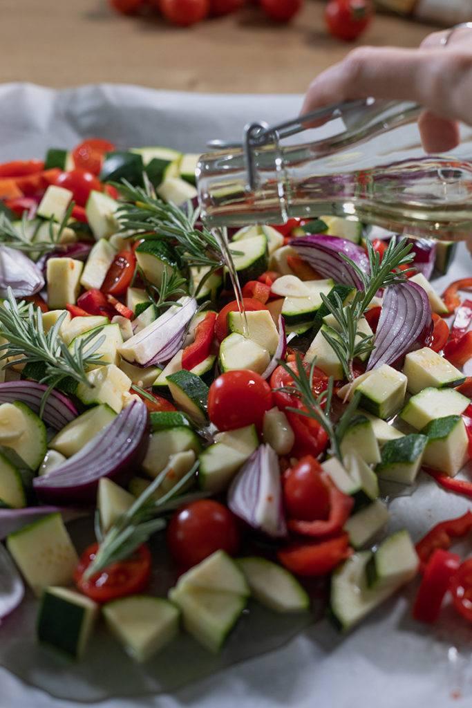 Geschnittenes Gemüse wird bevor es in den Ofen kommt mit Oel beträufelt