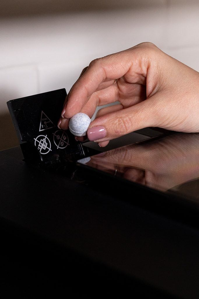 JURA Reinigungstablette in den Pulverschacht für die Reinigung des JURA Kaffeevollautomaten einwerfen