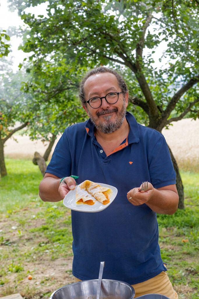 Weinviertler Musiker Jimmy Schlager mit der mit Marillentraum fuer einen Kindertraum Marillenmarmelade gefuellten Palatschinke im Marillengarten