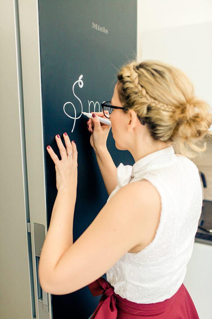Foodbloggerin Verena Pelikan beim Beschriften vom Miele Kuehlschrank Blackboard Edition in ihrem SchlossStudio im Schloss Coburg zu Ebenthal