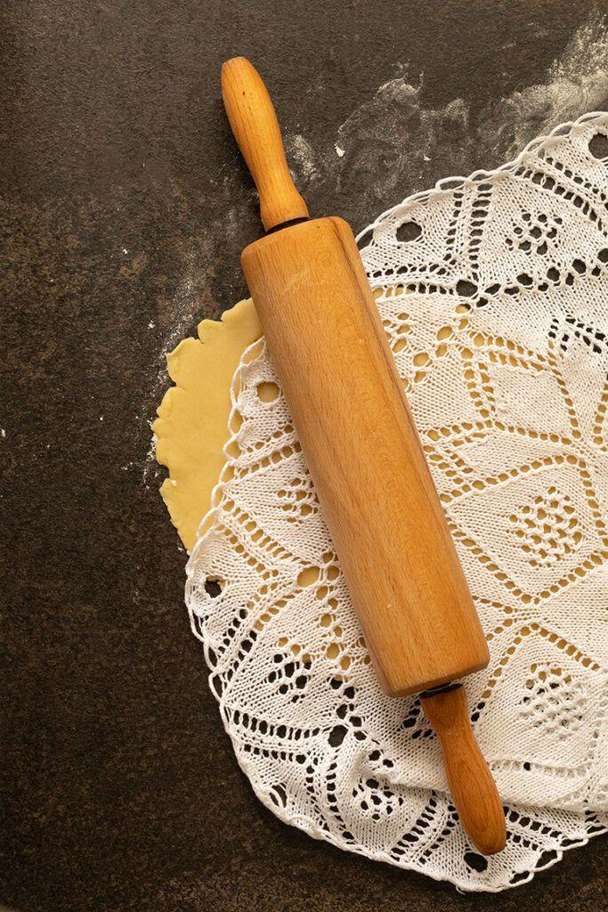 Alte Haekeldecke wird mit Nudelholz auf den Muerbteig gedrueckt fuer Kekse mit Haekeldeckenmuster nach einem Rezept von Sweets & Lifestyle®