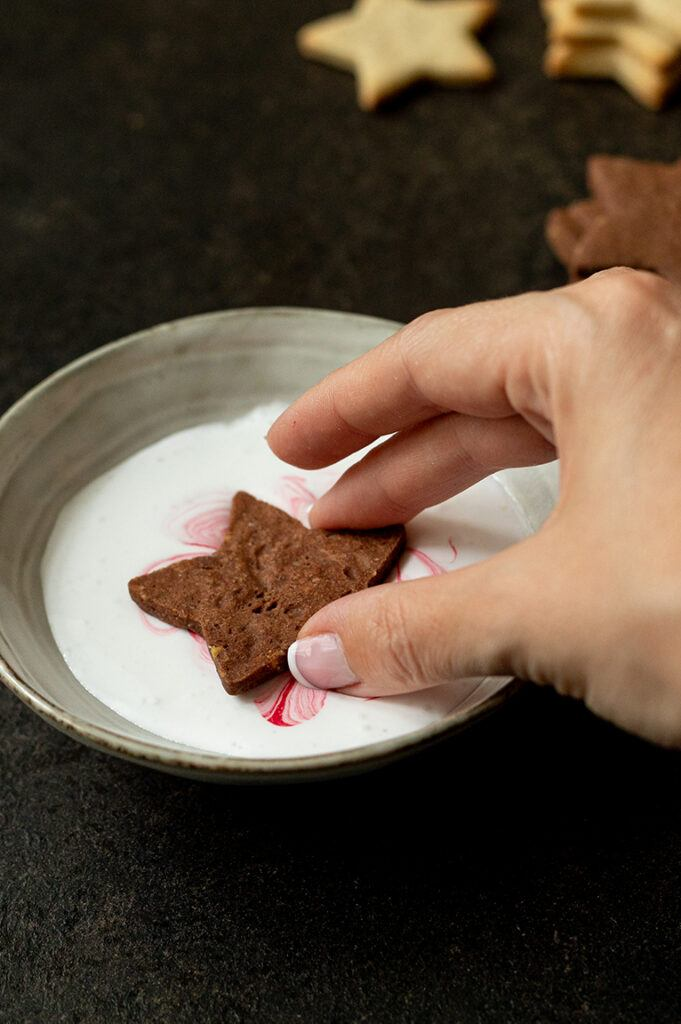 Kekse in die Eiweissglasur mit Lebensmittelpastenfarbe tunken um den Marmoreffekt für die Kekse mit marmorierter Eiweissglasur zu erzielen