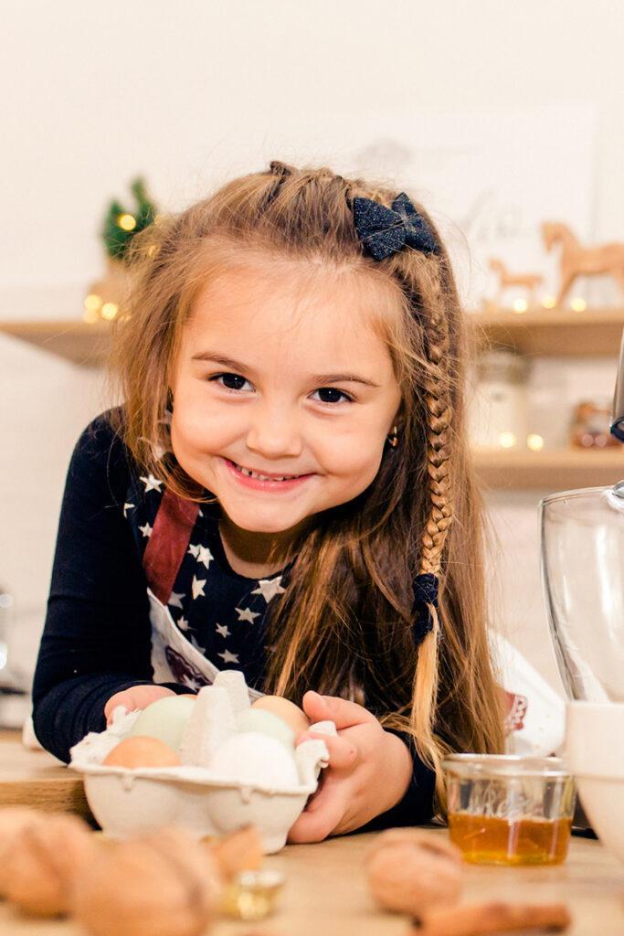 Glueckliches Kind beim Weihnachtskekse backen Backkurs mit Verena Pelikan von Sweets & Lifestyle® in ihrem Kochstudio SchlossStudio im Schloss Coburg zu Ebenthal