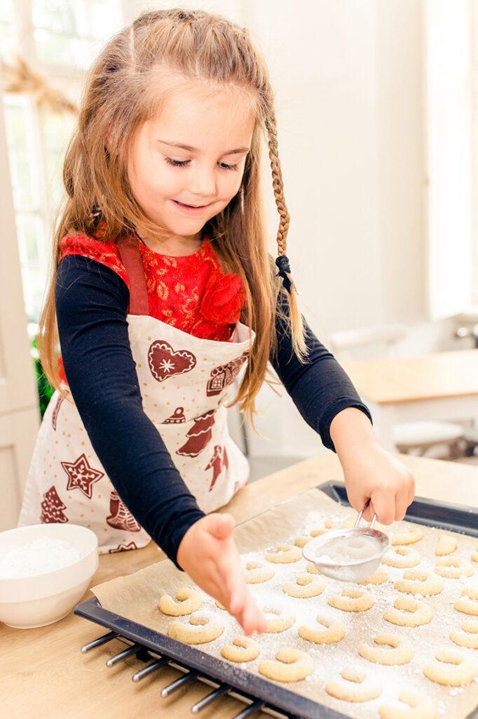 Glueckliches Kind bestreut selbst gemachte Vanillekipferl mit Staubzucker beim Weihnachtskekse backen Backkurs im Kochstudio SchlossStudio von Verena Pelikan