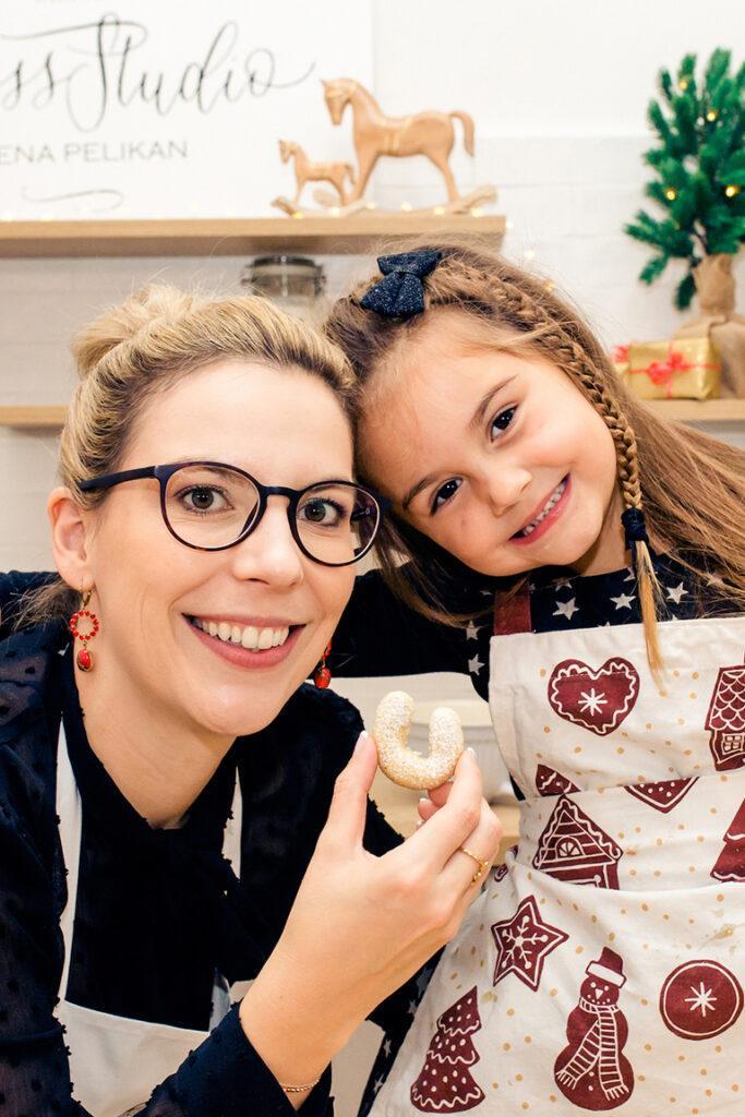 Verena Pelikan mit gluecklichem Kind beim gemeinsamen Plaetzchen backen fuer Weihnachten beim Weihnachtskekse Backkurs fuer Kinder im SchlossStudio Kochstudio