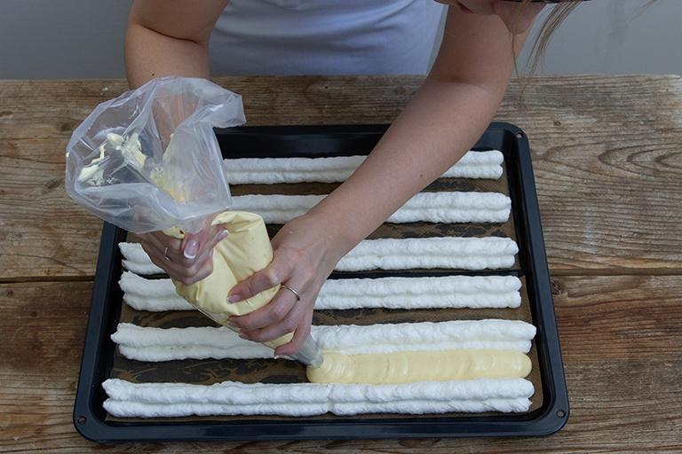 Biskuitmasse mit Spritztuelle in die Zwischenraeume der Baiserstreifen spritzen fuer die Kardinalschnitte von Sweets & Lifestyle®