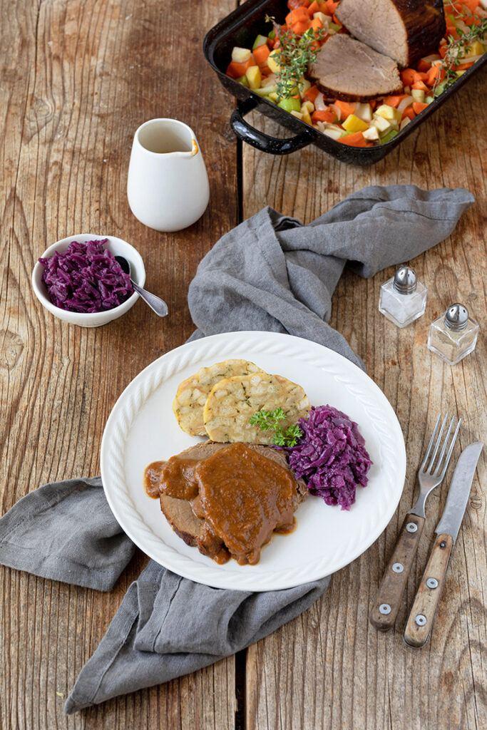 Geschmorter Rinderbraten mit Wurzelsauce serviert mit Serviettenknoedel und Rotkraut nach einem Rezept von Sweets & Lifestyle®