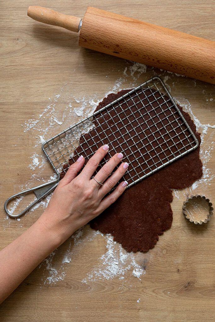 Kuchengittter auf den Schoko-Nuss-Teig druecken um das Gittermuster in den Teig zu bekommen