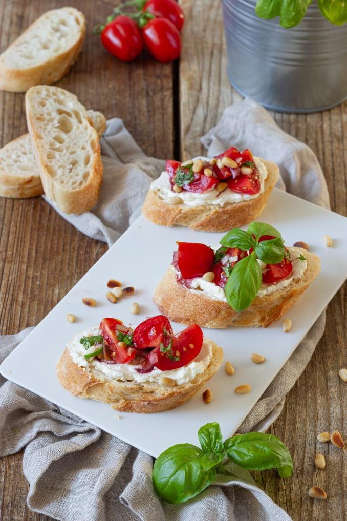 Leckere Bruschetta mit Tomaten Frischkaese und geroesteten Pinienkernen als einfaches Fingerfood nach einem Rezept von Sweets & Lifestyle®