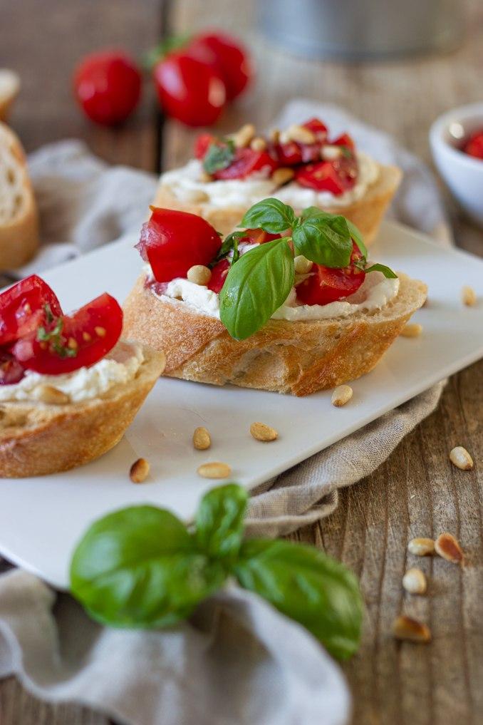 Knusprige Bruschetta mit frischen Tomaten verfeinert mit Frischkaese und geroesteten Pinienkernen nach einem Rezept von Sweets & Lifestyle®