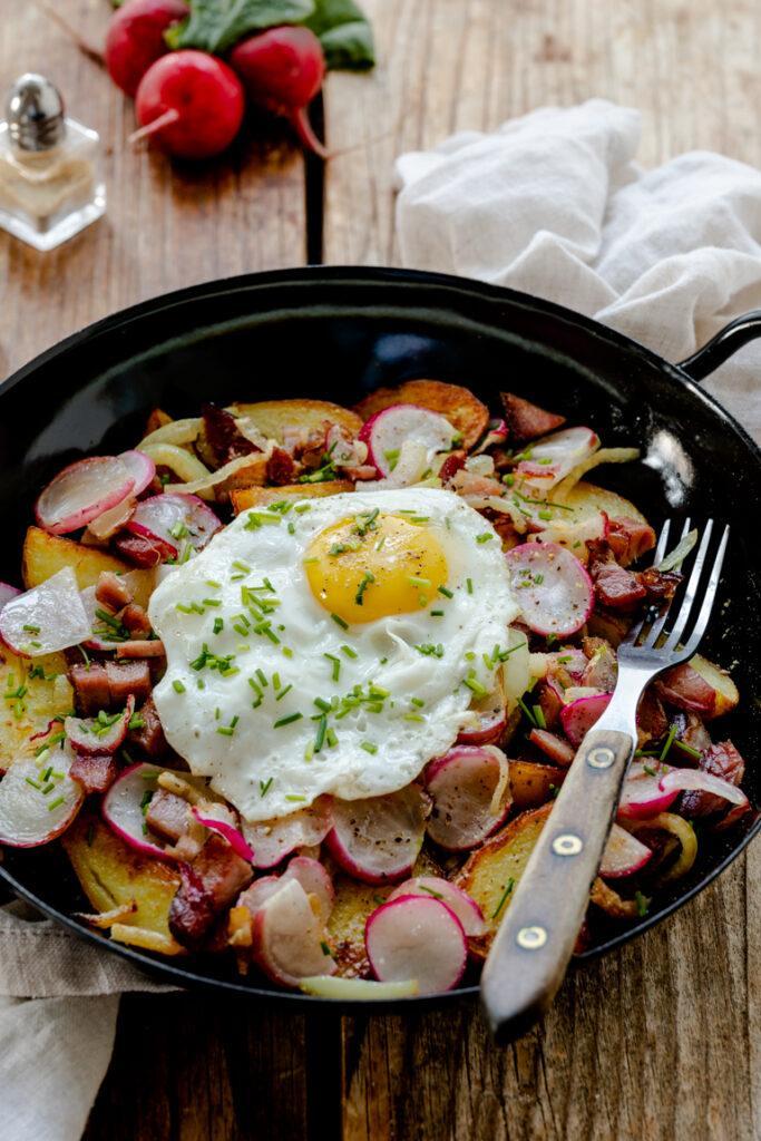 Eine leckere Resteverwertung ist die Restepfanne mit Kartoffeln Geselchtem Radieschen und Spiegelei als herzhaftes Fruehstueck nach einem Rezept von Sweets & Lifestyle®