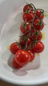 Rispentomaten mit Olivenoel vorbereiten fuer das Grillen im Backofen