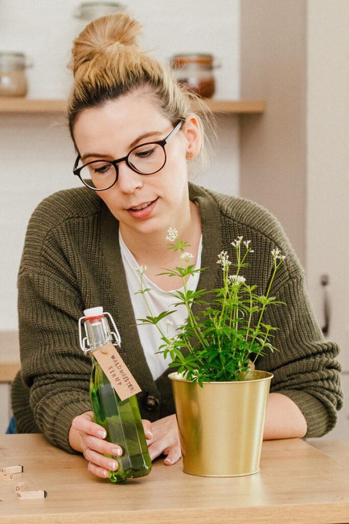 Oesterreichs Top Foodbloggerin Verena Pelikan mit dem frisch abgefuellten Waldmeistersirup aus echtem Kraut nach ihrem Rezept