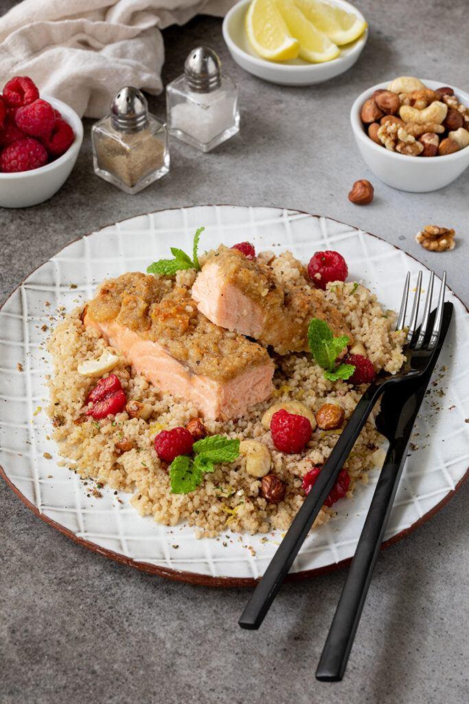 Leckerer Ofenlachs mit Parmesan Nuss Kruste serviert auf einem Couscous Himbeer Salat mit Nuessen nach einem Rezept von Sweets & Lifestyle®