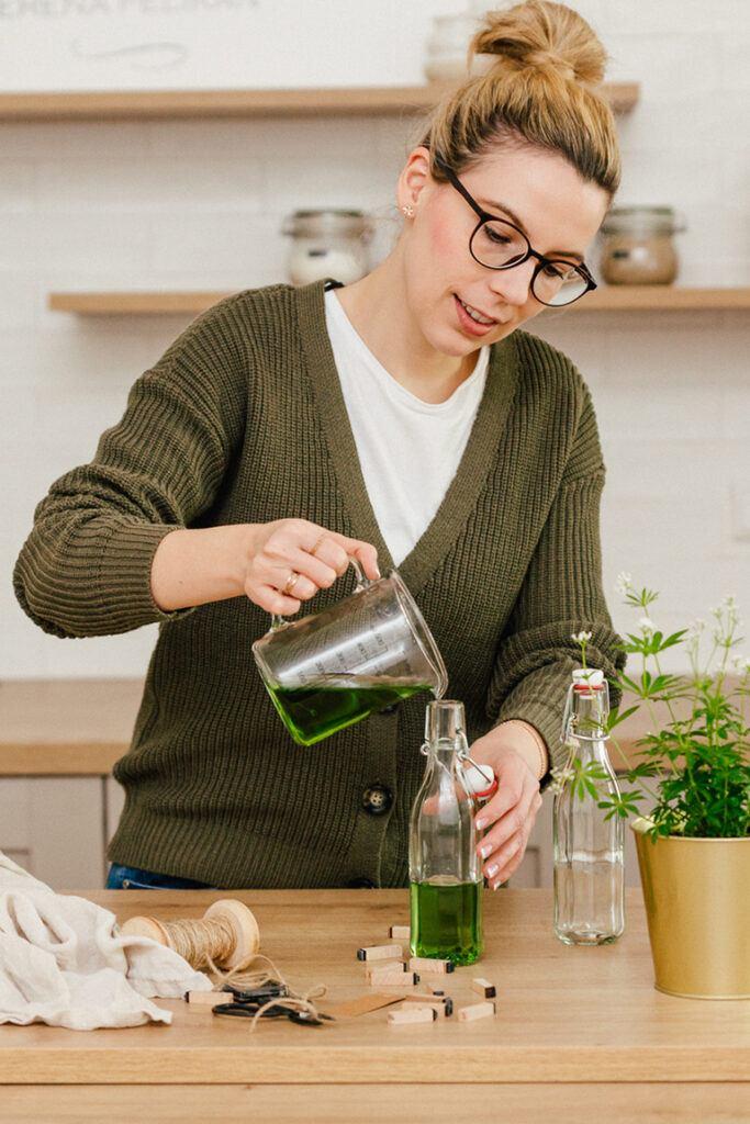 Foodbloggerin Verena Pelikan fuellt den Waldmeistersirup aus frischem Waldmeister nach ihrem Rezept in die Flasche